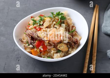 Arroz frito con mariscos, verduras, jengibre y perejil sobre fondo oscuro. Cocina asiática. Comida vegetariana Foto de stock