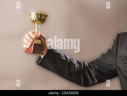 El hombre de negocios tiene el trofeo de oro del campeón, el concepto de éxito y victoria