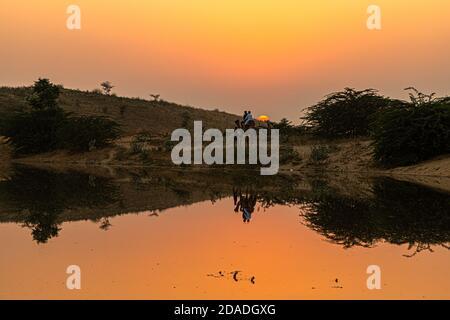 vista de la hermosa puesta de sol y el reflejo de camello en el estanque.