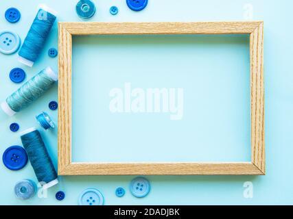 Bobinas de hilo y botones en tonos azules en un fondo azul