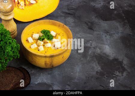 Sopa de calabaza con crema, pan y perejil fresco en un plato de metal rústico sobre fondo negro grunge. Vista superior, espacio de copia