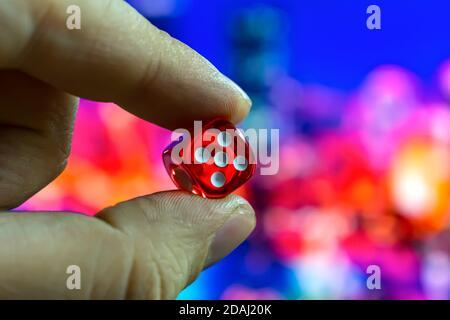 Un hombre sostiene dados rojos en sus manos entre los dedos sobre el fondo de las luces nocturnas de la ciudad