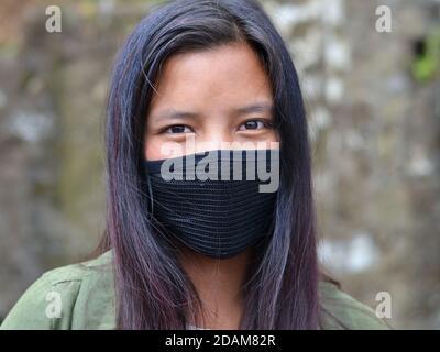 Hermosa niña India Monpa cubre su cara con una máscara de cara negra reutilizable, no médica.