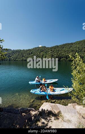 Familia con dos niños en dos kayaks en el hermoso Lago Levico en Valsugana (Valle de Sugana), Trentino Alto Adige, Italia, Europa