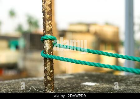 Una cuerda está atada en un nudo alrededor de un poste de la cerca, cuerda atada nudos del enganche en un poste de hierro oxidado aislado del fondo.