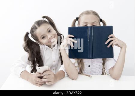 Contra la vieja escuela moderna. Colegiala mantenga teléfono móvil smartphone moderno mientras su amiga disfrute de libro viejo como almacenamiento de datos analógicos. Tecnología contra la experiencia. Nueva generación de demandas educativas.