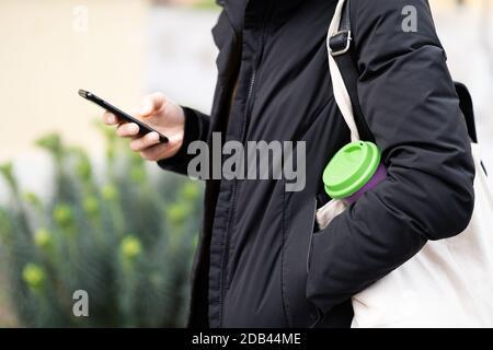 Las manos femeninas sostienen la taza de café reutilizable al aire libre. Llévate tu café para llevar con una taza de viaje reutilizable. Cero residuos. Concepto de estilo de vida sostenible.