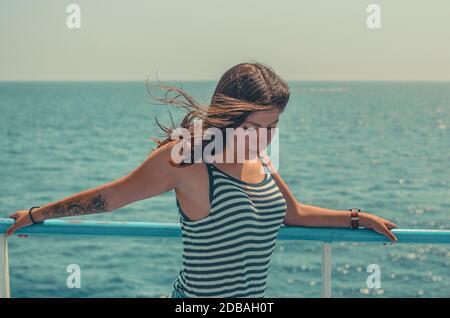 retrato de una mujer joven hermosa con el pelo negro con un tatuaje en su brazo en una camiseta ajustada a rayas sobre un fondo de mar azul