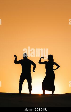 siluetas de un feliz joven pareja y chico en un fondo de naranja puesta de sol en el desierto de arena