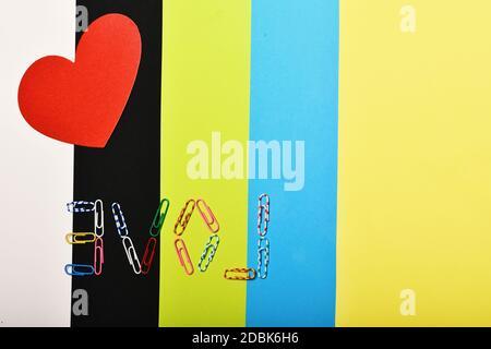 Corazón de papel rojo sobre fondo de colores, vista superior. El amor y el concepto de relación. Tarjeta del Día de San Valentín con espacio de copia. Colorido clips de papel formando la palabra AMOR.