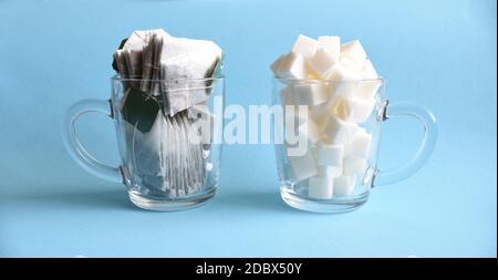 Dos tazas de vidrio transparente llenas de azúcar blanco refinado y bolsas de té sobre fondo azul. Concepto de consumo frecuente de té con azúcar como daño a la salud