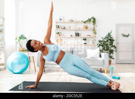 Concepto de fitness en casa. Determinada mujer negra trabajando en la alfombra deportiva en interiores, haciendo ejercicio de tablón lateral
