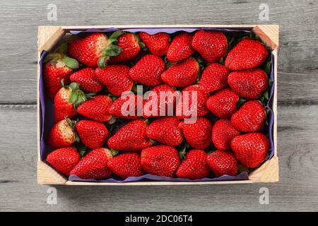 Vista superior de la tabla en la pequeña caja de fresas de supermercados colocado sobre el mostrador de madera de color gris.