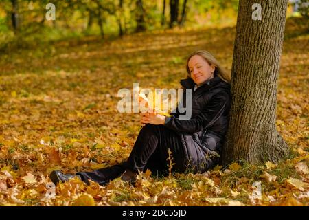 Una hermosa joven rubia se sienta en las hojas caídas de otoño en el parque, apoyándola contra un tronco de árbol. La chica tiene hojas de arce amarillo