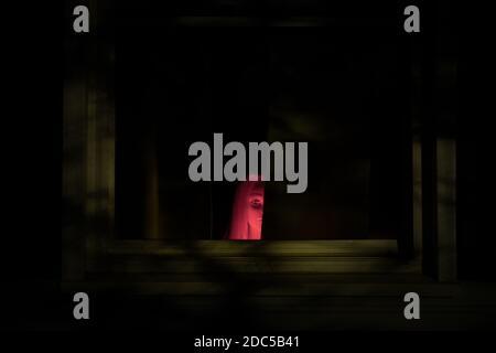 Una imagen espeluznante, con una cabeza de maniquín de una niña en rojo de iluminación peeking desde detrás de una cortina. Bueno para Halloween.