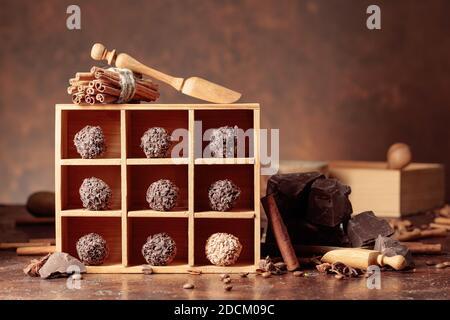 Trufas de chocolate con trozos de chocolate rotos. Chocolate, especias e ingredientes en una mesa marrón.