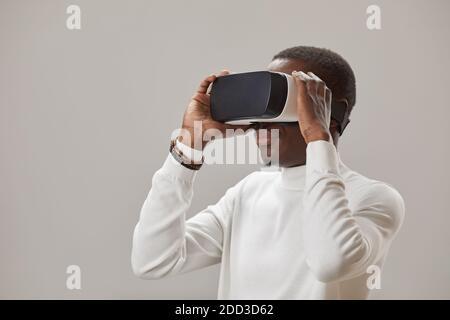 Joven africano en gafas virtuales jugando en realidad virtual juego contra el fondo gris