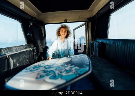 Mujer joven quitando la tabla de surf del coche mientras está de pie en la playa
