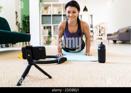 Sonriente mujer joven grabación de vídeo en la cámara mientras hace empuje ups en casa