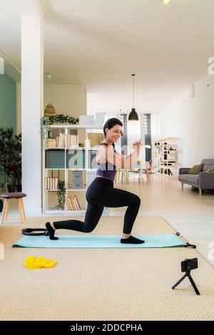 Mujer joven haciendo ejercicios de lunges y grabando en la cámara inicio