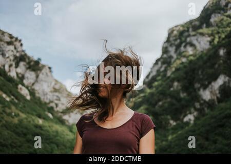 Mujer adulta mediana con pelo largo y marrón contra la montaña rango Foto de stock