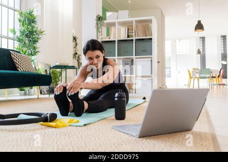 Mujer joven sonriente mirando fuera mientras hace ejercicio de estiramiento sentado en casa