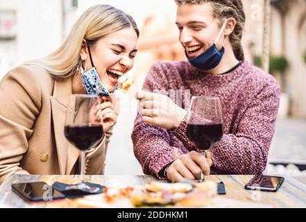 Pareja joven enamorada usando máscaras de cara abierta pasándose bien En el bar de vinos al aire libre - felices amigos viajeros disfrutando del almuerzo juntos en el jardín del restaurante