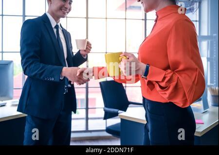 Socios de negocios que le sacuden las manos con una taza de café. Concepto de cooperación empresarial.