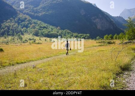 Un hombre aislado camina por un sendero en una llanura bajo las montañas Sibillini (Marche, Italia, Europa)