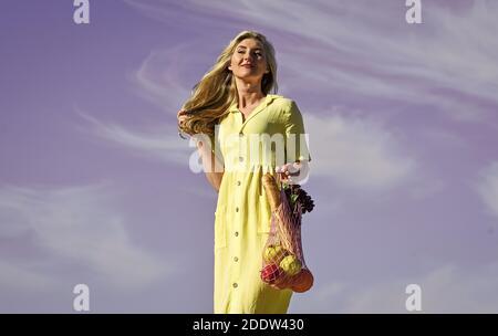 Cero residuos. Concepto sin plástico. Bolsas de algodón y malla reutilizables para ir de compras. Niña verano día cielo azul fondo. Eco consciente. La mujer lleva frutas y verduras en una bolsa ecológica. Estilo de vida sostenible.