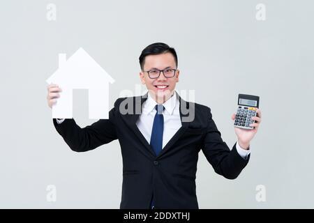 Agente de hombre asiático mostrando modelo de casa con calculadora para real concepto de financiación inmobiliaria e inversión Foto de stock