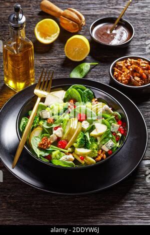 ensalada de pera con cubos de queso azul, brócoli, hojas de espinacas, nueces caramelizadas y semillas de granada en un plato negro sobre mesa de madera, acción de gracias