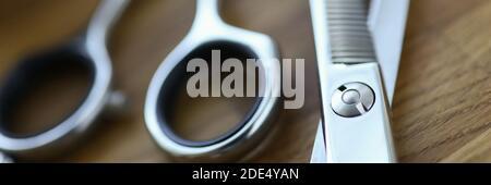Cerca, tijeras de acero barbero están acostadas sobre la mesa
