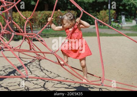 hermosa niña de tres años con un vestido rojo en un cuerda web en el patio de juegos