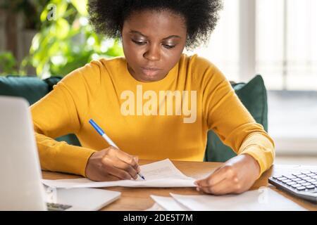 Mujer negra empleada o gerente de trabajo remoto en casa durante el cierre, toma notas con el lápiz, trabaja con documentos en papel. Trabajador de oficina durante una pande