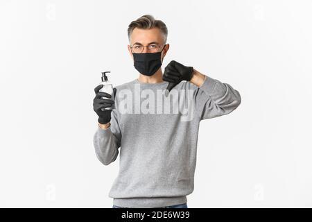 Concepto de coronavirus, estilo de vida y cuarentena. Retrato de un hombre de mediana edad con mascarilla médica y guantes no se recomienda antiséptico, mostrando la mano