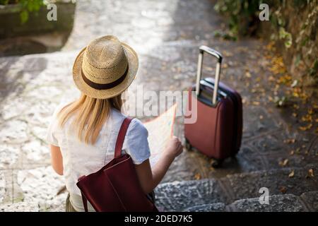 Una chica viajera con maleta está sentada en las escaleras de piedra en otoño. Mujer joven turista está buscando dirección