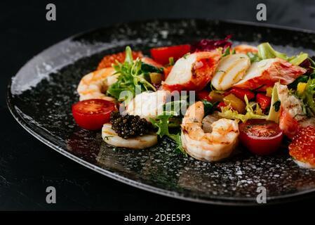 ensalada con gambas, verduras y carne de cangrejo sobre fondo negro