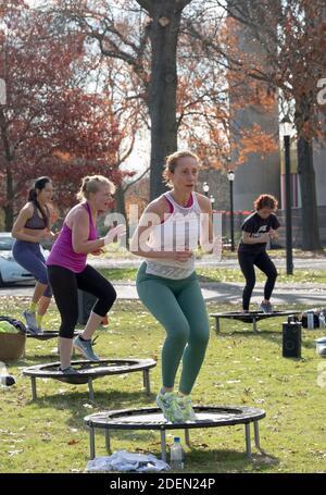 Mujeres en una clase urbana de rebounding bailando mientras en un pequeño trampolín. En Flushing Meadows Corona Park en Queens, Nueva York.