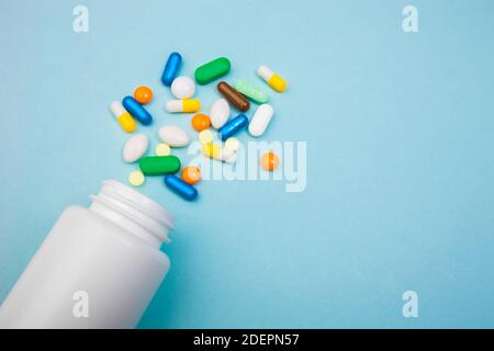 Tabletas y cápsulas multicolor, botella blanca para tabletas, píldoras de medicina farmacéutica sobre fondo azul, analgésico contra enfermedades