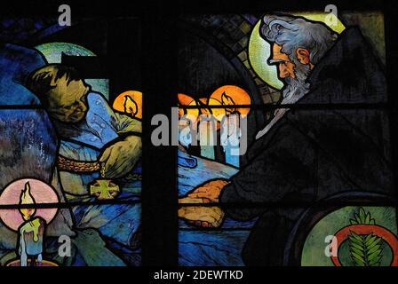 Vigilia a la luz de las velas por el lecho de muerte del teólogo bizantino y misionero San Cirilo, representado por el influyente artista Art Nouveau Alphonse Mucha en su vívida vidriera de 1930 para la Capilla del Nuevo Arzobispo en la Catedral de San Vito en Praga, capital de la República Checa / República Checa. La obra de arte, una alegoría de Cristo que bendice a las naciones eslavas, presenta escenas de la vida de los 'Apóstoles a los eslavos' Cirilo y su hermano Metodio, así como el patrón checo san Wenceslao, duque de Bohemia, y su abuela, San Ludmila.
