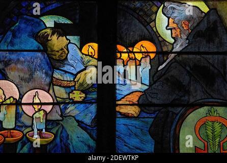 Vigilia a la luz de las velas en el lecho del teólogo bizantino y misionero San Cirilo, representada por el influyente artista Art Nouveau Alphonse Mucha en su vívida vidriera de 1930 para la Capilla del Nuevo Arzobispo en la Catedral de San Vito en Praga, capital de la República Checa / República Checa. La obra de arte, una alegoría de Cristo que bendice a las naciones eslavas, presenta escenas de la vida de los 'Apóstoles a los eslavos' Cirilo y su hermano Metodio, así como el patrón checo san Wenceslao, duque de Bohemia, y su abuela, San Ludmila.