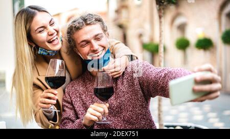Pareja joven enamorada de la máscara abierta tomando selfie En el bar de vinos al aire libre - felices amantes del milenio disfrutando del almuerzo juntos en el patio del restaurante