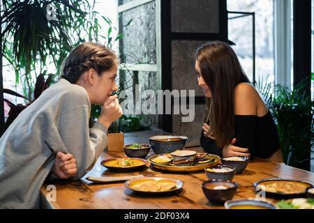 Dos chicas de escuela secundaria chismoreando en un café asiático.