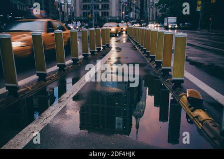 edificio empire state reflejado en el charco durante la puesta de sol, cielo púrpura con taxis amarillos que conducen por la ciudad de broadway new york
