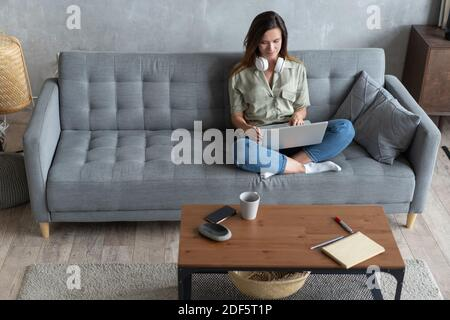 Mujer joven haciendo trabajo de investigación para su negocio. Mujer sonriente sentada en el sofá navegando por el sitio web de compras en línea