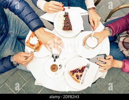 Los amigos se agrupan con pasteles, café y leche en el restaurante del bar - primer plano de las manos de las personas con smartphones con parte superior punto de vista