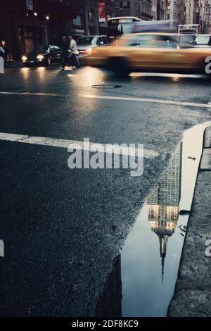 edificio empire state reflejado en el charco durante el anochecer, con taxis amarillos que conducen calle abajo, ciudad de nueva york