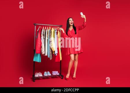 Vista completa del tamaño del cuerpo de la impresionante señora alegre que hace selfie que demuestra el armario aislado sobre fondo de color rojo brillante