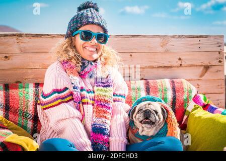 Invierno y colorido retrato feliz de la joven hermosa alegre y perro sentado al aire libre juntos - personas y animales concepto - cielo azul en la espalda